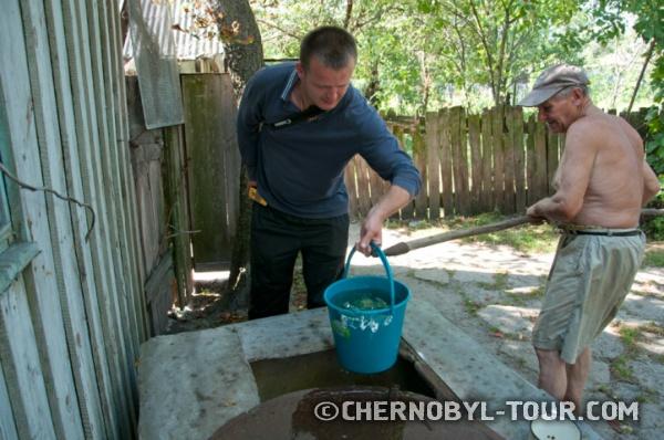 Чернобыль-ТУРист помогает самосёлу Ивану набирать воду в колодце.